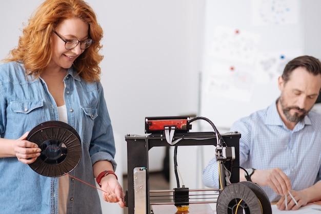 Leuke opgetogen, aangename vrouw die een gloeidraadspoel vasthoudt en deze aanpast aan de 3d-printer terwijl ze ernaast staat
