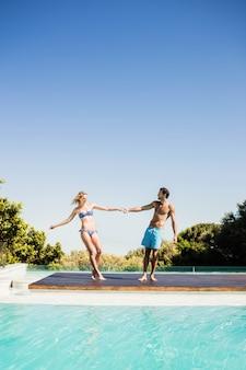 Leuke paar hand in hand bij het zwembad