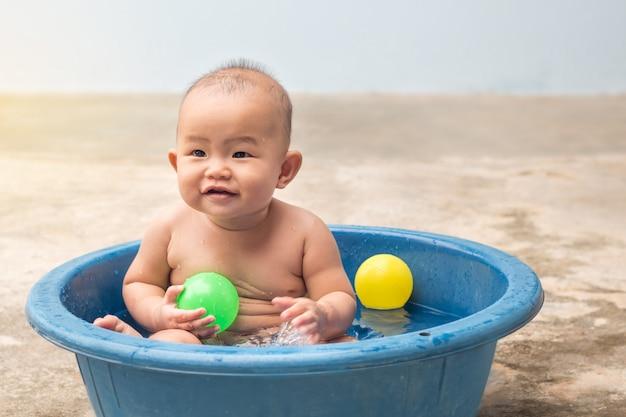Leuke pasgeboren baby spelen bal in het plastic bekken tijdens douche