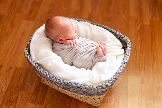 Leuke pasgeboren babyjongen in de grijze mand. kleine handen en voeten van het kind. baby verpakking