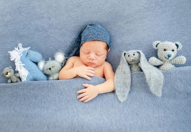 Leuke pasgeboren jongen die onder blauwe deken ligt
