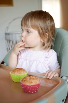 Leuke peuter, babymeisje die in kinderstoel voeden die een muffin eten. heerlijk gezond zelfgebakken eten voor kinderen