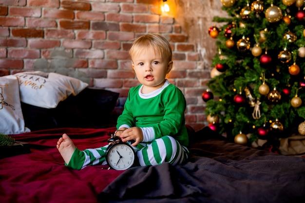 Leuke peuter in pyjama zit in de buurt van de kerstboom