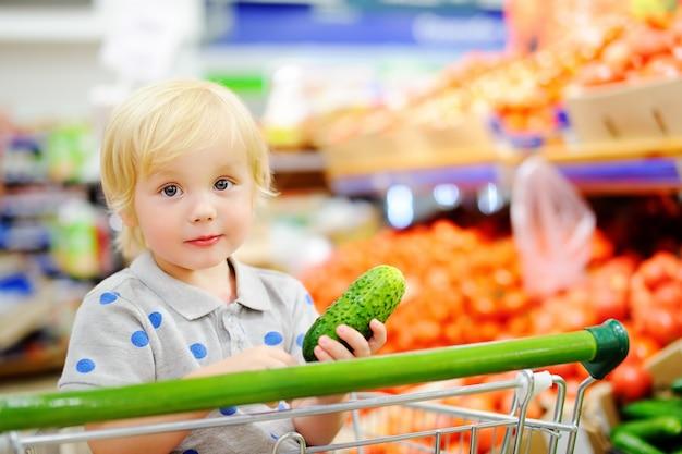 Leuke peuter jongen zit in het winkelwagentje in een supermarkt of een supermarkt. gezonde levensstijl voor jong gezin met kinderen