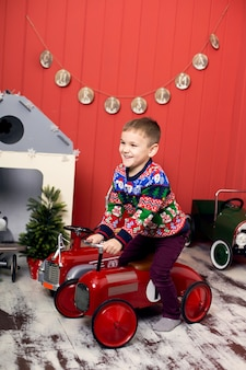 Leuke peuter speelt met speelgoed rode auto's. rijdt op een speelgoedmachine met typemachine. gelukkige jeugd.