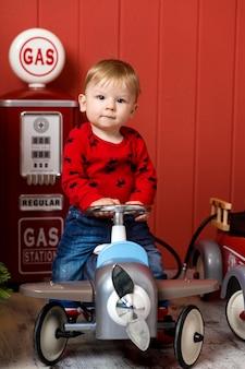 Leuke peuter speelt met speelgoedauto's. rijdt op een speelgoedmachine met typemachine. gelukkige jeugd