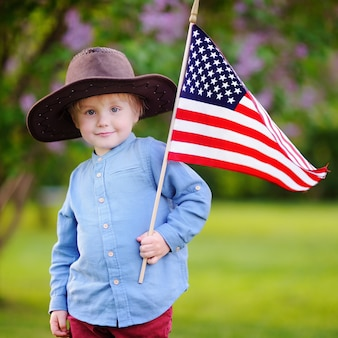 Leuke peuterjongen die amerikaanse vlag in mooi park houdt