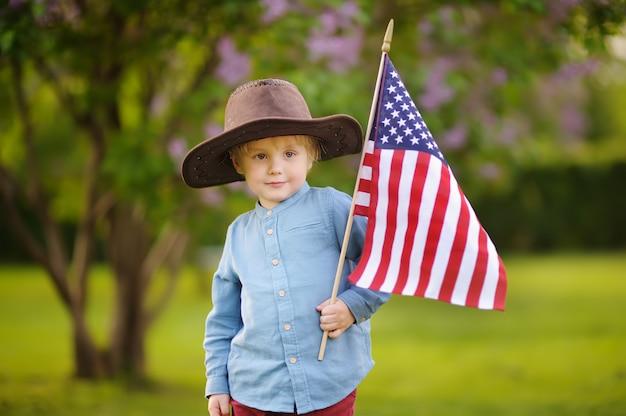 Leuke peuterjongen die amerikaanse vlag in mooi park houdt.