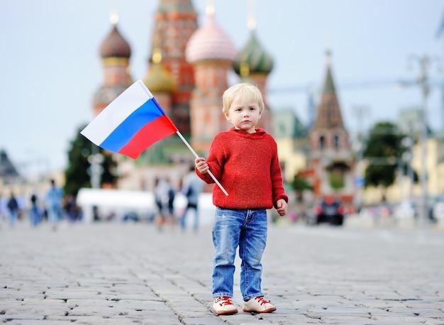 Leuke peuterjongen die russische vlag met rode vierkant en vasilevsky-afdaling houdt