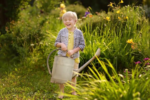 Leuke peuterjongen het water geven installaties in de tuin bij de zomer zonnige dag.