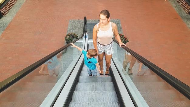 Leuke peuterjongen met jonge moeder die zich op roltrap bij winkelcentrum bevindt