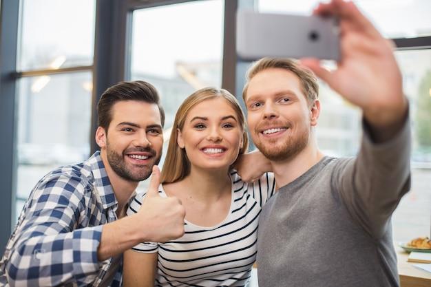 Leuke, plezierige man die samen met zijn vrienden staat en een smartphone vasthoudt terwijl hij een selfie maakt