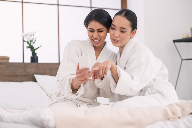 Leuke positieve aantrekkelijke vrouwen die samen op het bed zitten terwijl ze naar de foto's op hun smartphone kijken