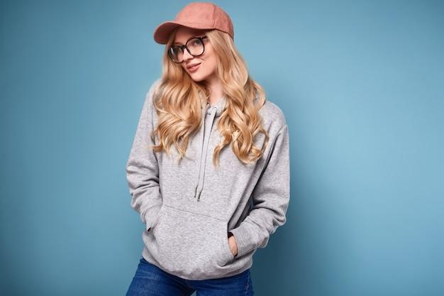 Leuke positieve blonde vrouw in een roze baseball cap