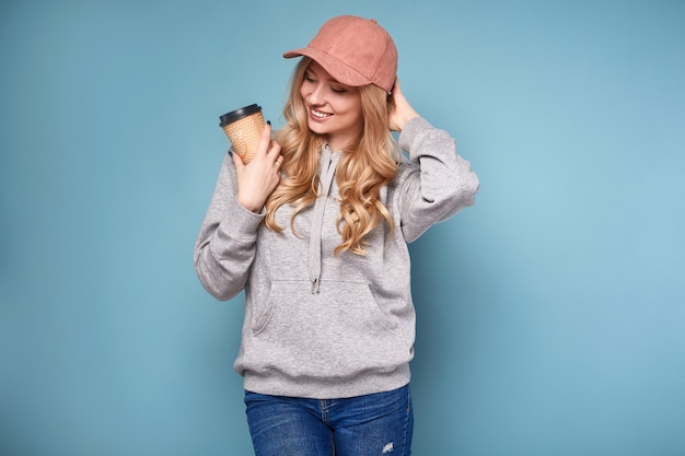 Leuke positieve blondevrouw in roze glb met koffie