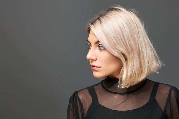 Leuke positieve jonge blanke vrouw draagt trendy zwarte top en transparante jurk met dromerige peinzende gezichtsuitdrukking, maakt plannen voor kerstvakantie, kijkt weg en glimlacht vreugdevol