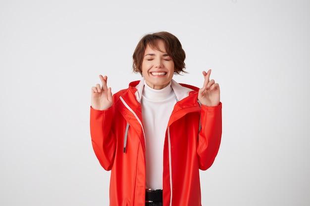 Leuke positieve jonge kortharige dame in witte golf en rode regenjas, bijt op de lippen, kijkt omhoog naar de kopie ruimte, kruist vingers en hoopt op geluk. staand.