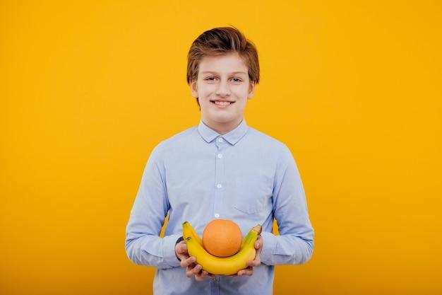 Leuke preteen kindjongen met fruit in de hand, in het blauwe shirt, geïsoleerd op gele muur