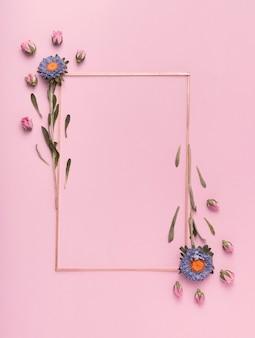 Leuke regeling van een verticaal kader met bloemen op roze achtergrond
