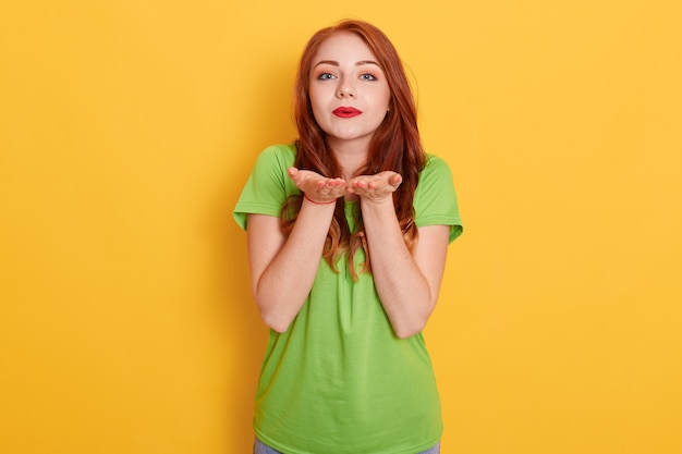 Leuke romantische roodharige vrouw permanent en verliefd lucht kus verzenden naar camera, genegenheid tonen, groene t-shirt dragen