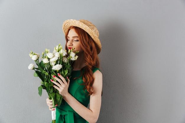 Leuke roodharige jonge vrouw met bloemen.