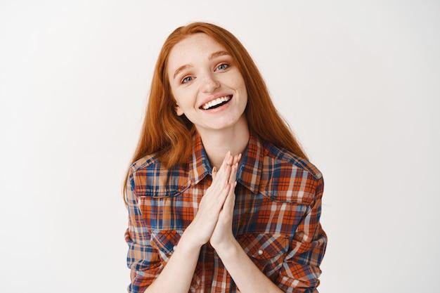 Leuke roodharige vrouw die om gunst vraagt. vrouw met rood haar en blauwe ogen smeekt teken en zegt alsjeblieft, glimlachend terwijl ze om hulp smeekt, witte muur