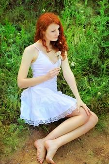 Leuke roodharige vrouw in witte jurk zittend op een gras in park met paardebloemen in haar handen.