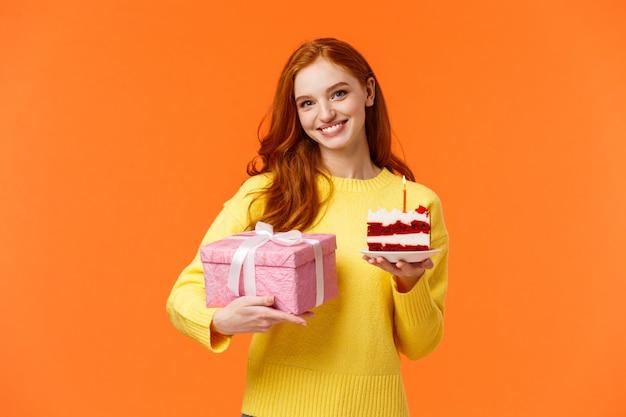Leuke roodharige vrouw komende partij met verpakt cadeau en stuk heerlijke b-day cake, vriend vragen