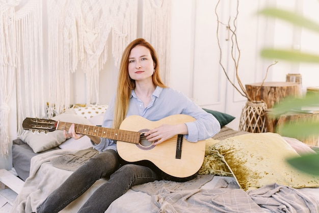 Leuke roodharige vrouw leert gitaar spelen, zittend op bed