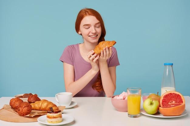 Leuke roodharige vrouw met een vlecht zit aan een tafel, heeft ontbijt