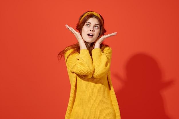 Leuke roodharige vrouw op de gele achtergrond van de sweaterglamour. hoge kwaliteit foto
