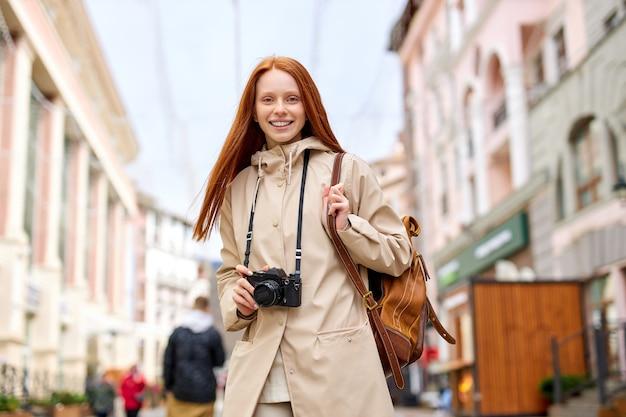 Leuke roodharige vrouw reiziger met warme glimlach foto nemen op film retro camera tijdens het wandelen in stedelijke stad, portret van trendy vriendelijke dame in vrijetijdskleding met rugzak bij koud lenteweer