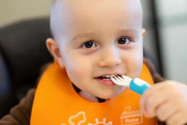 Leuke schattige baby van 18 maanden oud die plastic vork in zijn mond neemt en met voedsel speelt