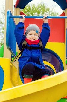 Leuke schattige jongen van twee jaar in een blauwe jas en rode sjaal speelt op een lichte speeltuin