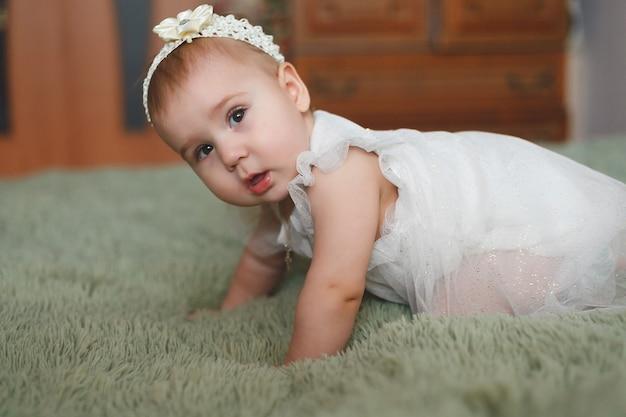 Leuke schattige pasgeboren baby van 3 motten met luiers. hapy klein meisje of jongen kijken naar de camera en witte jurk. droog en gezond lichaam en huid voor kinderen concept. babykamer