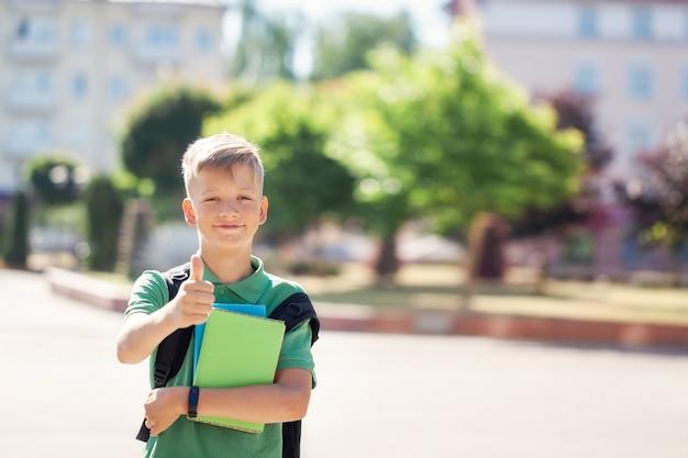 Leuke schooljongen buitenshuis op zonnige dag. tiener met zijn rugzak en boeken houden