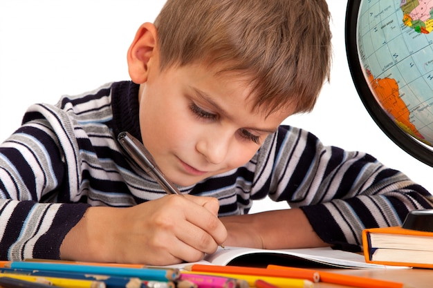Leuke schooljongen die in een notitieboekje schrijft