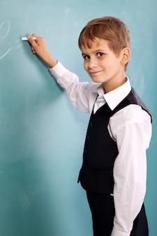 Leuke schooljongen die op een schoolbord schrijft