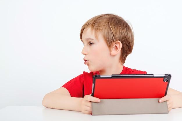 Leuke schooljongen die zijn huiswerk met digitale tablet thuis doet.