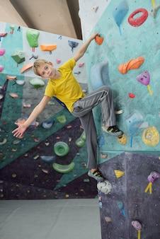 Leuke schooljongen in activewear die met één hand door kleine rots op klimmuur houdt en zijn armen gestrekt houdt
