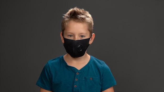 Leuke schooljongen in herbruikbaar gezichtsmasker, donkerblauw t-shirt glimlachend in de camera terwijl hij in de studio staat