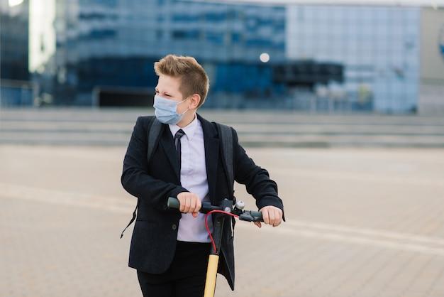 Leuke schooljongen met beschermend masker besturen van een scooter in een stad.