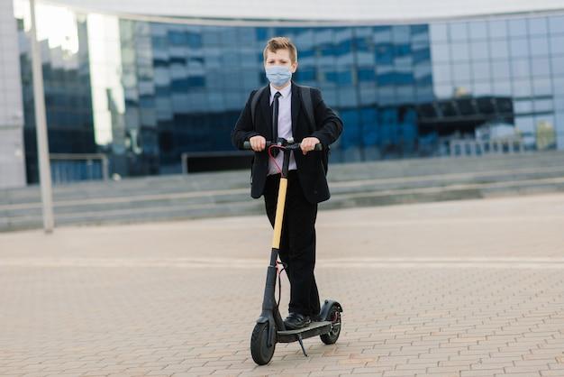 Leuke schooljongen met beschermend masker die een autoped in een stad drijft.