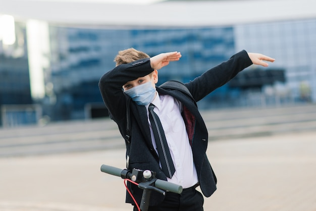 Leuke schooljongen met beschermend masker een scooter besturen in een stad.