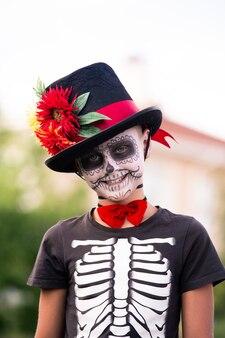 Leuke schooljongen met geschilderd gezicht in halloween kostuum van skelet met elegante zwarte hoed die voor camera staat en naar je glimlacht