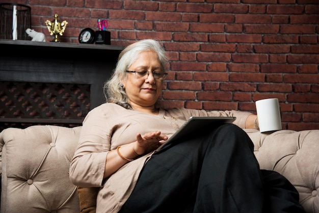 Leuke senior indiase aziatische dame zittend op fauteuils stoel of bank leesboek of met behulp van tab- of laptopcomputer