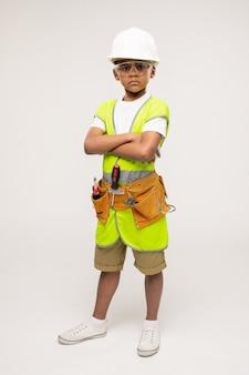 Leuke serieuze kleine reparateur in vrijetijdskleding, veiligheidshelm, beschermende bril en uniformjas die zijn armen bij de borst kruist