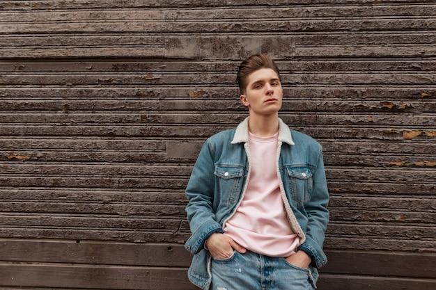 Leuke sexy jongeman met kapsel met stijlvol blauw spijkerjasje in roze modieus t-shirt in de buurt van vintage houten muur in de stad. mode stedelijke man in mooie trendy vrijetijdskleding wandelingen. street style.