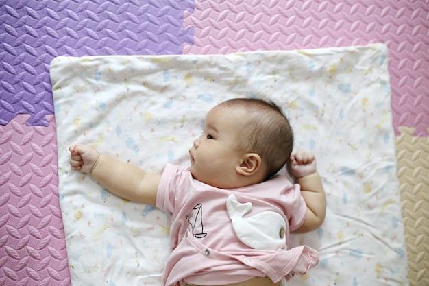 Leuke slimme aziatische pasgeboren babyslaap met teddy konijnstuk speelgoed op roze zachte bed thuis.