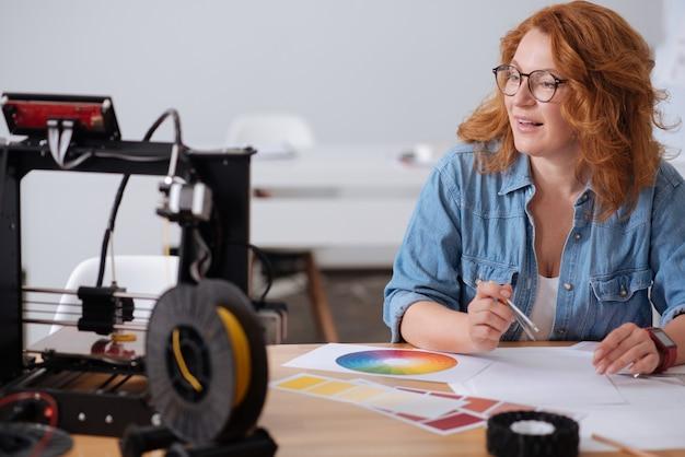 Leuke slimme hardwerkende vrouw die aan tafel zit en naar de 3d-printer kijkt terwijl ze wat tekeningen maakt